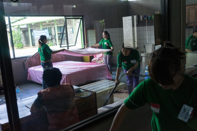 Caption from exhibition: April 25, 2014 - Jakarta, Indonesia. Aspiring domestic workers practice making beds and vacuuming in a training centre on the outskirts of the capital, as a trainer oversees their work. Some domestic workers use a doll to learn how to wash, change diapers and take care of newborns and infants. They also take language and cooking classes. © Thomas Cristofoletti / Ruom