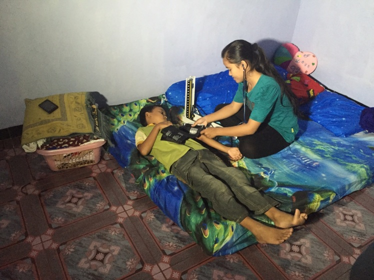 Nisa demonstrating the use of the stethoscope and blood pressure machine on her brother