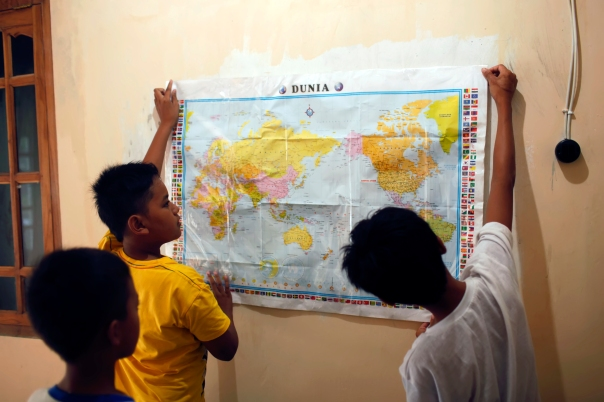 Chairul, Dirga and Ari decorate the library walls with the maps brought by Ristanti.