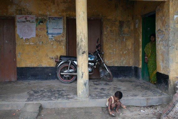 A toddler playing outside the Shologhar Union Council office opposite the village boat dock as his mother looks over.