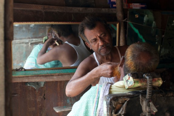 A barber carefully trims the beard of his client at the Sreenagar Bazaar in Munshiganj.